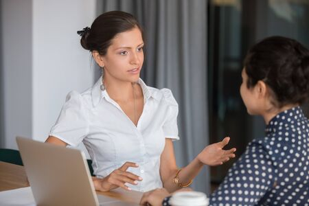 Multi-ethnic millennial women office workers sit at desk working on project discussing common task together, mentor explain corporate goals to apprentice give instructions helping, teamwork concept