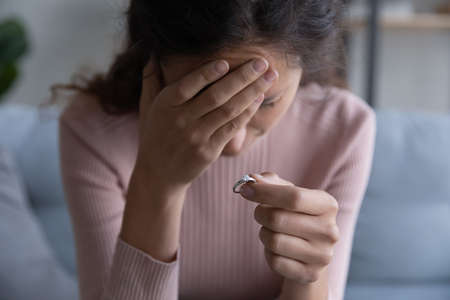 Close up focus on frustrated desperate millennial woman holding engagement ring in hand, denied getting married. Stressed young girl making decision breaking up with fiancee, betrayal divorce concept. Banco de Imagens
