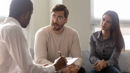Disappointed couple at reception with family therapist. African american doctor listening man in bad mood. Family relationship disorder concept. Psychology session with coach Stock Photo