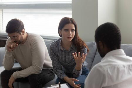Unhappy man and woman argue at family therapist reception. African american doctor listening woman in bad mood. Family relationship disorder concept. Girlfriend talks about problems with boyfriend