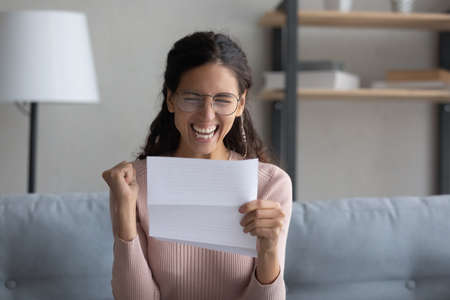 Overjoyed young attractive lady in eyewear holding paper letter, celebrating business success. Emotional millennial woman making yes gesture, feeling excited about personal achievement at home.