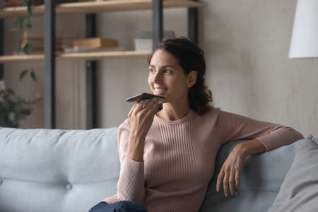 Happy young woman relaxing on comfortable sofa, sending audio message, sharing news with friends. Pretty smiling lady enjoying pleasant free weekend time alone at home, activating voice assistant.