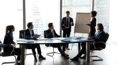 Two diverse coaches mentors giving flip chart presentation, training staff, explaining strategy at corporate meeting in modern boardroom, employees colleagues presenting financial report, results