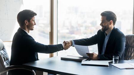 Smiling satisfied hr manager recruiter shaking successful candidate hand after job interview, congratulating with hiring, happy business partners handshaking, celebrating good deal Standard-Bild