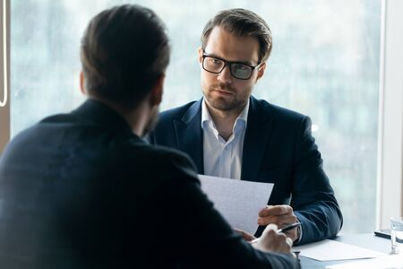 Serious attentive HR manager wearing glasses looking at job applicant, holding cv, listening to candidate on interview, strict employer, recruiter making decision about hiring, difficult negotiations