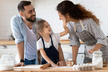 Happy cute little preschool girl spreading flour on cheerful parents. Laughing married couple having fun with small adorable kid daughter, playing together at free time, enjoying family activity. 版權商用圖片
