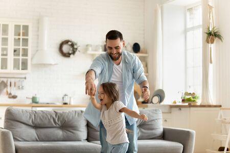 Aktiver junger Vater, der Händchen einer süßen kleinen Tochter im Vorschulalter hält und im modernen Wohnzimmer zu energiegeladener Popmusik tanzt. Glückliche Familie verschiedener Generationen, die zu Hause zusammen Spaß hat.