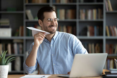Happy smiling businessman wearing glasses playing with paper plane at workplace, sitting at desk, having fun during break, enjoying rest after work done, new opportunities and success Stock fotó