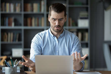 Unhappy shocked man having problem with broken or discharged laptop, looking at screen, amazed guy wearing glasses reading bad news in email, stressed businessman surprised by financial report