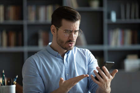Unhappy irritated young man wearing glasses having problem with broken or discharged smartphone, indignant angry confused businessman looking at phone screen, reading bad news in message