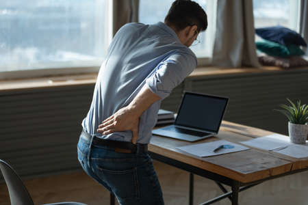 Rear view young man suffering from sudden backache, getting out of uncomfortable chair at workplace, touching lower back, unhealthy businessman student office worker feeling discomfort