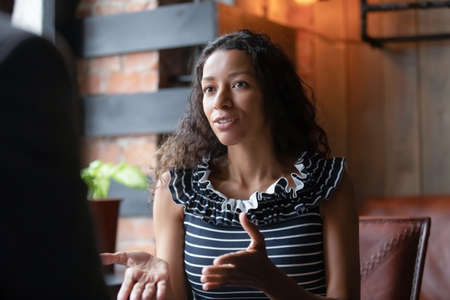 African American millennial woman seated in coffeehouse talking chatting with friend or colleague during coffee break, biracial young female involved in interesting conversation meeting in cafe