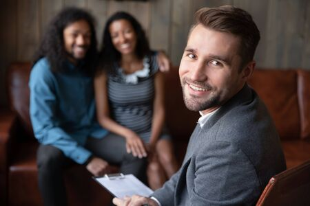 Smiling male Caucasian psychologist look at camera consult multiracial couple with relationships problems, successful confident man counselor or coach head family psychological session or therapy Stock Photo