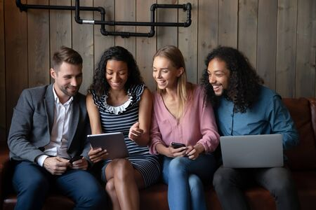 Overjoyed young people sit on couch in coffeeshop have fun watching funny videos on devices together, happy multiracial friends relax on sofa in cafe laugh using modern gadgets with wireless Internet Archivio Fotografico
