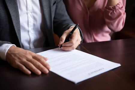 Close up of caucasian couple close deal in coffeehouse put signature on contract buy house together, young spouses make agreement sign paperwork document after successful discussion in cafe
