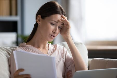 Upset woman reading bad news in letter close up, holding papers and touching forehead, unhappy sad young female looking at laptop screen, checking bills, bankruptcy, eviction or dismissal notice