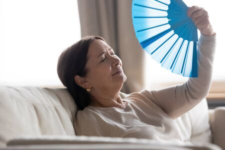 Tired middle aged woman with closed eyes waving blue paper fan, suffering from heat, sitting on couch at home, sweaty mature female feeling unwell, cooling in hot summer weather, high temperature
