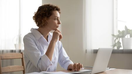 Thoughtful young female doctor thinking of medical question at workplace. Serious doubtful woman professional medic wearing white coat thinking of problem solution doing online healthcare research.