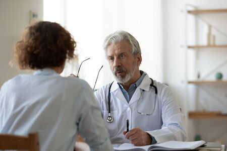 Professional senior male physician consulting female patient in hospital. Old doctor examining young adult woman at medical visit. Senior man therapist talking to client at healthcare checkup meeting