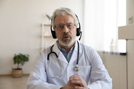 Older male doctor therapist wearing headset videoconferencing talking to web camera consulting virtual patient online by video conference call chat. Telemedicine, telehealth concept. Webcam view. Stock Photo