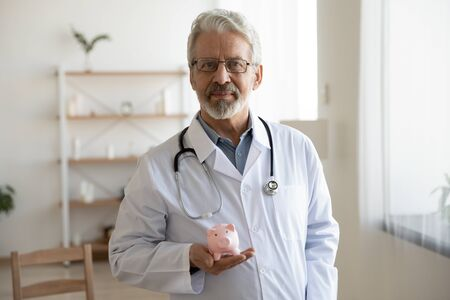 Senior older male doctor physician holding piggy bank box looking at camera standing in hospital. Healthcare insurance fees financial cost and money savings for medical health cafe expenses concept.