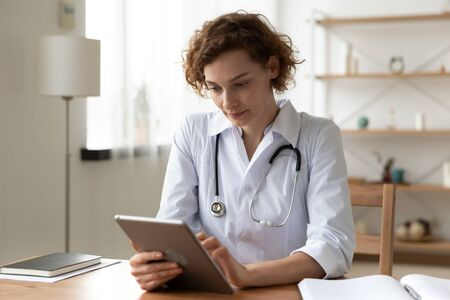 Serious professional doctor wearing white coat and stethoscope holding modern touchscreen gadget using digital tablet computer at work. Healthcare tech medical data network and telehealth concept.