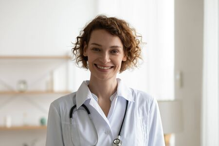Smiling young adult woman doctor wearing white medical coat and stethoscope head shot close up portrait. Happy female physician, therapist, general practitioner looking at camera standing in hospital. Banco de Imagens