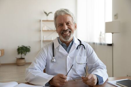 Portrait of friendly smiling senior adult healthcare professional therapist sitting at workplace. Happy confident older male doctor physician wearing white medical coat stethoscope looking at camera.