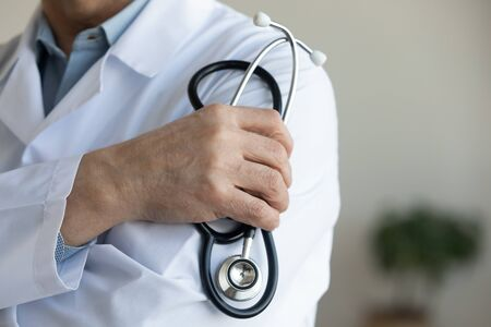Senior male doctor wearing white medical coat holding stethoscope in hand. Older man cardiologist, physician, therapist close up view. Healthy heart, cardiac diseases treatment, healthcare concept.