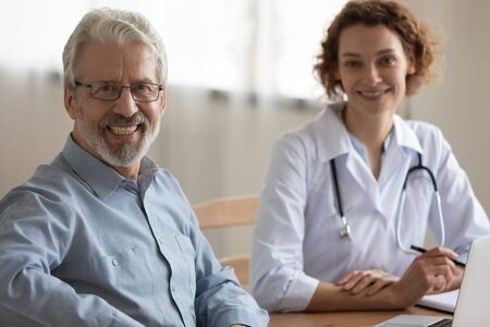 Happy healthy male elder senior adult 60s patient looking at camera visiting physician. Smiling older man sitting at doctors hospital checkup meeting. Geriatrics, elderly medical health care concept