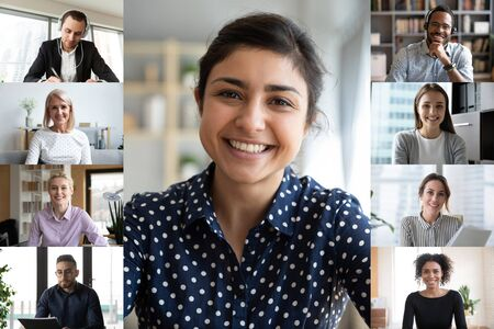 Smiling young indian female employee talk speak on video call with diverse colleagues, multiracial coworkers employees have webcam conference using modern app, engaged in web online briefing
