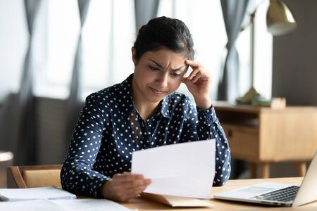 Head shot stressed unhappy millennial indian girl looking through paper document. Upset hindu woman feeling nervous about bank debt notification, worrying about financial problems, dismissal letter.