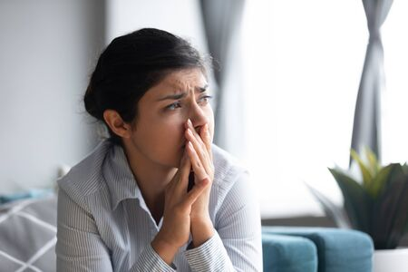 Depressed young indian girl suffering from mental stress, thinking of difficult decision. Frowning powerless millennial hindu woman worrying about personal problems, feeling desperate alone at home.