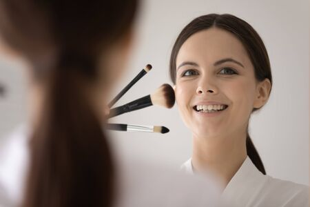 Smiling young woman look in mirror posing with brushes, get ready at home in morning, happy millennial girl makeup artist do make up, learn with beauty video tutorials, cosmetics, beautician concept Archivio Fotografico