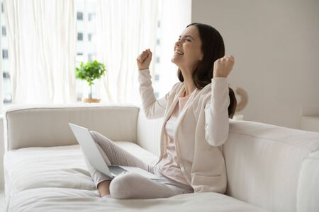 Overjoyed millennial girl sit on sofa ta home feel excited euphoric winning online lottery on laptop, happy young Caucasian woman triumph read good news on internet, get promotion letter on computer