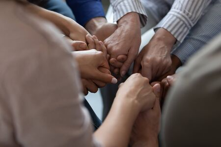 Close up mixed race business people holding hands together, support and unity concept. Diverse colleagues joining in team building activity, staff training concept, teamwork relationship.