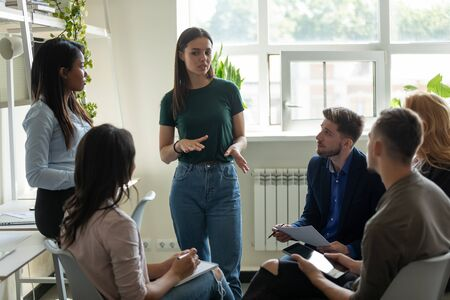 Serious female leader, mentor holding briefing for multiracial team interns in office, teaching students, plan to subordinates. Confident businesswoman at company meeting with diverse colleagues.