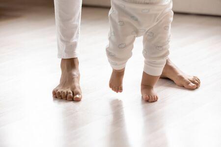 Gros plan sur un petit nourrisson biracial faisant ses premiers pas sur le plancher en bois de la maison tenant les mains de sa mère, un petit bébé afro-américain apprend à marcher avec des soins de soutien à la mère, concept de garde d'enfants