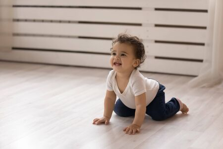 Happy small biracial baby girl child creep on all fours on warm wooden floor at home, smiling cute little african American infant toddler go on hands and knees, play indoors, childcare concept