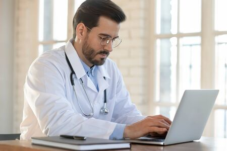 Serious young Caucasian male doctor in white medical uniform sit at desk in hospital consult client on laptop online, man GP or physician fill patient medical card use Web application form on computer
