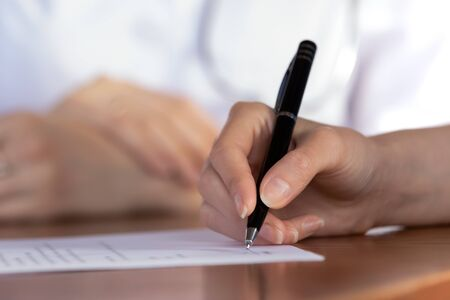 Close up of female patient put signature on paper document close deal with doctor in hospital, woman client sign paperwork contract making health insurance agreement with GP at meeting Archivio Fotografico