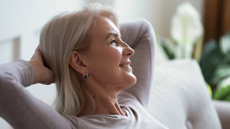 Close up of happy mature woman sit relax on sofa in living room breathing fresh air, smiling calm middle-aged female rest on couch at home daydreaming or enjoying leisure weekend, stress free concept Stock Photo
