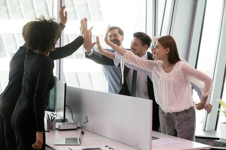 Group of diverse co-workers making profitable deal giving high five share common success celebrating victory moment, received great news about company leadership, team of lawyers won the case concept Stock Photo