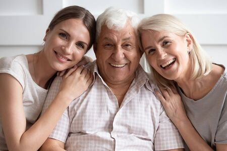 Portrait of happy adult family sit rest on couch smile for picture at home together, overjoyed senior parents hug embrace grownup daughter relax enjoy leisure weekend, look at camera posing