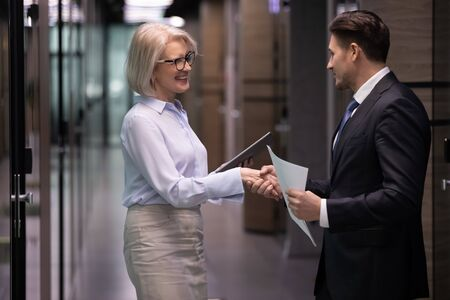 Mature and young businesspeople stand in office hall shake hands get acquainted greeting each other. Happy workmates handshake congratulating with promotion, business success or got rewarded concept Stockfoto