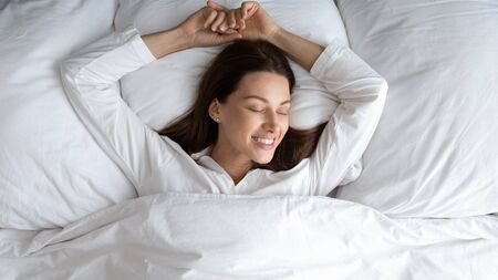 Top view blissful 30s woman in white comfy nightclothes lying in bed at home or hotel bedroom enjoy free day holidays, single female wake up feeling rested after healthy enough night sleeping concept