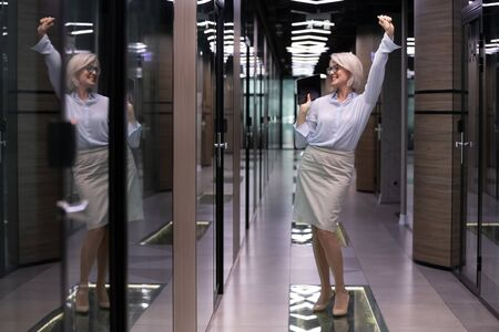 Elegant satisfied middle-aged businesslady company owner standing in office hallway dancing enjoy moment of business achievement and success, senior woman employee celebrate career advancement concept