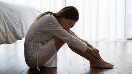 Sad young woman in white nightrobe sit barefoot on floor in bedroom leaned head to knees looking unhappy, suffers from loneliness, break up divorce with husband, hard decision about abortion concept