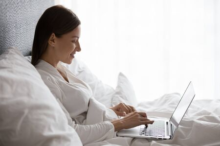 Fresh happy 30s woman sit on bed under warm blanket leaned on pillows use pc enjoy internet apps, start day in morning chat on-line with friend, e-dating e-commerce websites user, check e-mail concept