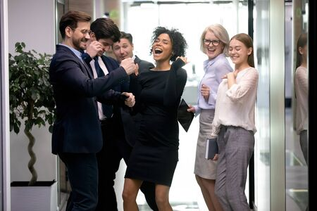 Six diverse office employees gathered in hallway celebrating successful contract signing, got unbelievable business opportunity, reward and financial corporate success, profitable deal results concept